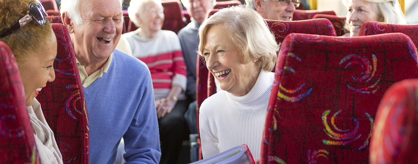 older man with two older women on a bus laughing